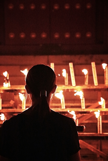 A woman praying before a rack of lit candles.
